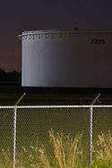 A giant oil tank stands on a dark night in the far suburbs of Chicago, behind a tall security fence.