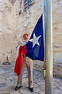 ranger bringing down Texas flag at The Alamo