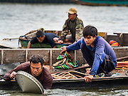 06 OCTOBER 2015 - BANGKOK, THAILAND: Dive teams on salvage diver's boats rinse off pans full of scrap metal they brought up from the bottom of the Chao Phraya River in Bangkok. Divers work in two man teams on small boats in the Chao Phraya River. One person stays in the boat while the diver scours the river bottom for anything that can be salvaged and resold. The divers usually work close to shore because the center of the river is a busy commercial waterway with passenger boats and commercial freight barges passing up and down the river all day long. The Chao Phraya is a dangerous river to dive in. It's deep, has large tidal fluctuations, is fast flowing and badly polluted. The divers make money only when they sell something.     PHOTO BY JACK KURTZ