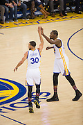 Golden State Warriors guard Stephen Curry (30) and Golden State Warriors forward Kevin Durant (35) high five at half court during a game against the Charlotte Hornets at Oracle Arena in Oakland, Calif., on February 1, 2017. (Stan Olszewski/Special to S.F. Examiner)