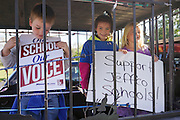 Children in a cage on the back of a pickup truck hold signs, one provided by MoveOn.Org (L) in Golden, Colorado October 2, 2014 at a protest against proposed changes to a history curriculum that would stress patriotism and discourage civil disobedience. The question of how U.S. teens learn history in public schools is the latest flash point in a liberal-conservative fight over national curricula that had previously focused on more scientific topics such as teaching creationism versus evolution.  REUTERS/Rick Wilking (UNITED STATES)