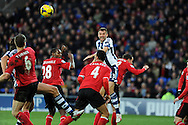 WBA's Gareth McAuley © is crowded out by Cardiff's defence as he goes for a header at goal.Barclays Premier league, Cardiff city v West Bromwich Albion at the Cardiff city Stadium in Cardiff, South Wales on Saturday 14th Dec 2013. pic by Andrew Orchard, Andrew Orchard sports photography.