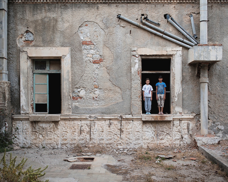Kurdish refugee children, Youssef, 14, and Diar, 13, standing in a window at the abandoned Lepida psychiatric hospital, in whose grounds the Leros &lsquo;Hot spot&rsquo; (an EU-run migrant&rsquo;s reception centre) has been built. <br /> <br /> Originally constructed, in 1930 by fascist Italy, as barracks for Italian soldiers serving in the aeronautical base of Portolago, it was then, for a short period after WWII, a re-education camp for the children of Greek Communists. In 1958, it was converted into the biggest psychiatric hospital in the country. The conditions for the patients were horrific and it was shut down in the late 1980s and the patients moved into smaller buildings in the grounds and elsewhere on the island.