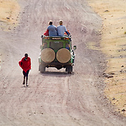 A clash of cultures and centuries: Masai teenagers walk past Western tourists on safari in Ngorngoro National Park, Tanzania.