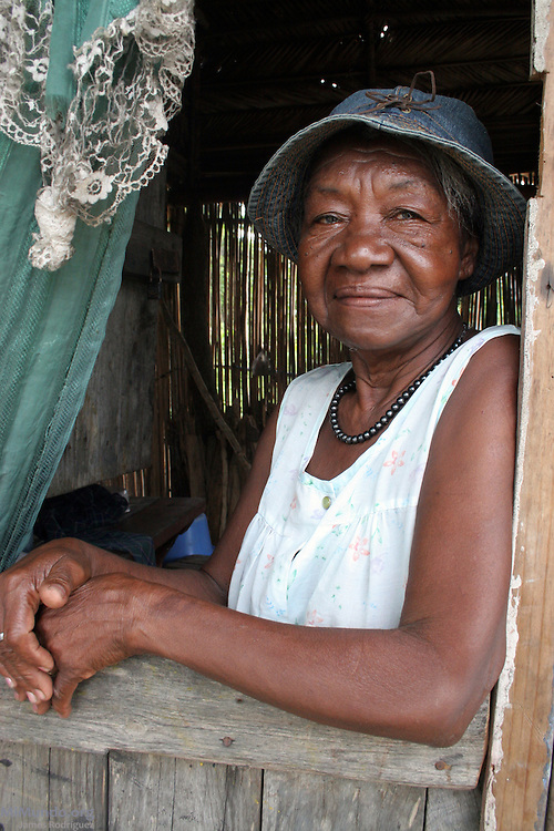 A local Garifuna woman from Barravieja Hamlet sits inside of a home. Garifuna communities, descendants of shipwrecked would-be African slaves, have inhabited most of the Central American Atlantic coast for over 200 years. Since the mid 1990's, mega-tourism projects threaten the continuity of the communities and the UNESCO-declared world heritage Garifuna culture and language as well. Tela, Atlántida, Honduras, July 2008.