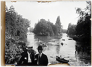 two young men in park with lake and rowing boats early 1900s