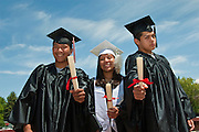 Three Native American youth proudly hold up their graduation diplomas