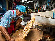 04 OCTOBER 2016 - BANGKOK, THAILAND:  A man separates peanuts from their skin at a Chinese peanut brittle stand at the Vegetarian Festival at the Chit Sia Ma Chinese shrine in Bangkok. The Vegetarian Festival is celebrated throughout Thailand. It is the Thai version of the The Nine Emperor Gods Festival, a nine-day Taoist celebration beginning on the eve of 9th lunar month of the Chinese calendar. During a period of nine days, those who are participating in the festival dress all in white and abstain from eating meat, poultry, seafood, and dairy products. Vendors and proprietors of restaurants indicate that vegetarian food is for sale by putting a yellow flag out with Thai characters for meatless written on it in red.    PHOTO BY JACK KURTZ