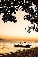 Silhueta de barco e pescador na Praia da Tapera ao por do sol. Florianópolis, Santa Catarina, Brasil. / Silhouette of a fisherman on a boat at Tapera Beach at dusk. Florianopolis, Santa Catarina, Brazil.