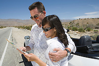 Young couple checking map at car in desert