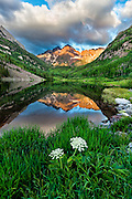 Early morning at Maroon Bells, near Aspen, Colorado. The mountains are reflected in a serene lake.
