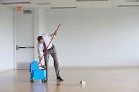 Business man using mop in empty room