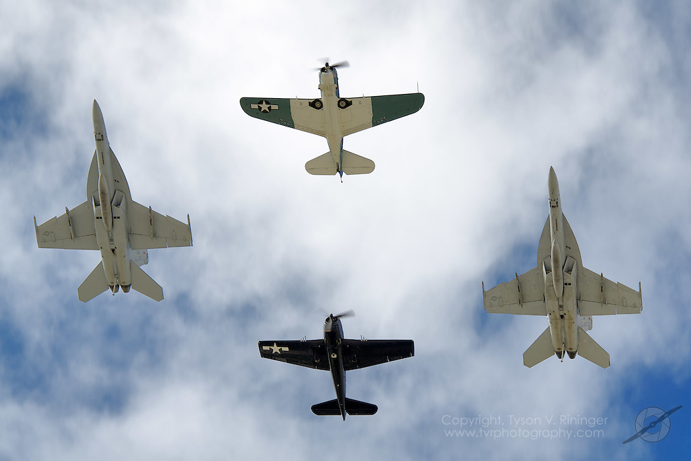 """An SB2C Helldiver flies lead with an F6F Hellcat in slot and two F/A-18F Super Hornets on each wing making up this unique four-ship formation. Flying the Hellcat is Ed Vesely and the F6F is Doug Rozendaal. The F/A-18F Super Hornets were flown by Lt. Brant """"Winthorp"""" Gresham and Lt. Alex """"Scribe"""" Armatas."""