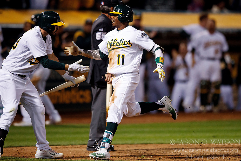 OAKLAND, CA - APRIL 04:  Rajai Davis #11 of the Oakland Athletics is congratulated by Matt Joyce #23 after hitting a two run triple and scoring on a throwing error by Danny Espinosa (not pictured) of the Los Angeles Angels of Anaheim during the seventh inning at the Oakland Coliseum on April 4, 2017 in Oakland, California. The Los Angeles Angels of Anaheim defeated the Oakland Athletics 7-6. (Photo by Jason O. Watson/Getty Images) *** Local Caption *** Rajai Davis; Matt Joyce