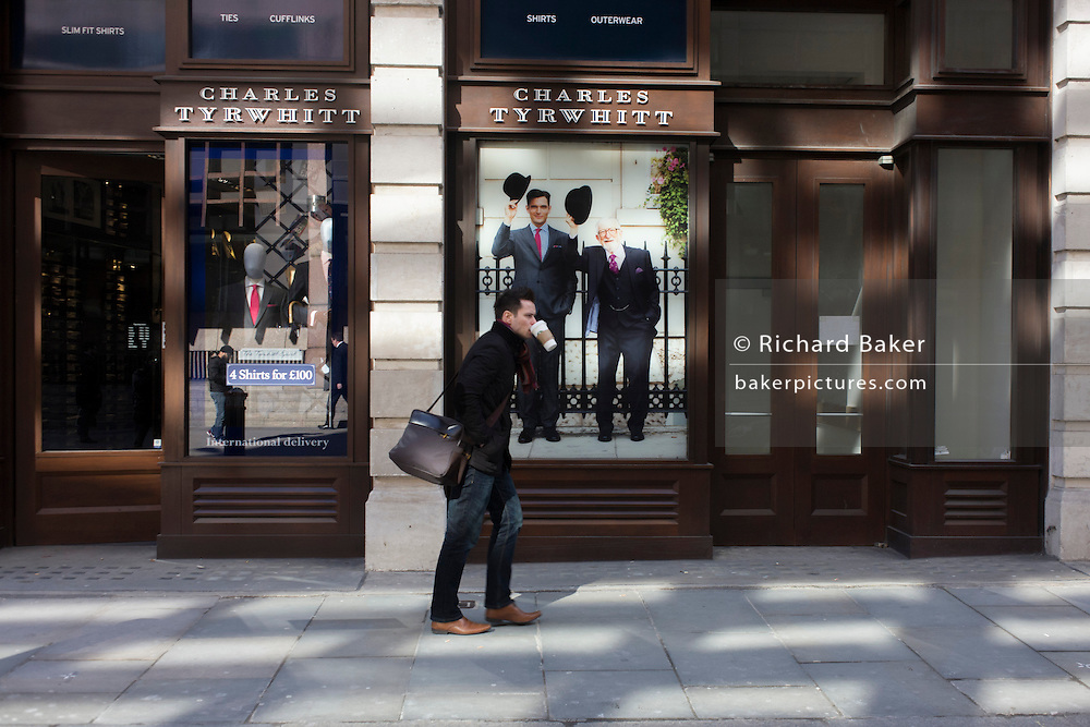 Carefully holding his coffee cup in his mouth, a Londoner walks past the Charles Tyrwhitt menswear outfitters at Liverpool Street in the City of London, the capital's heart of its financial district - a good location for suits and businesswear. A pair of Englishmen raise their bowler hats in a gesture from a previous era, when hats said much of your social standing, a summary of your position in the class system. In the 21st century though, the hat is largely an item of clothing to wear only for extreme cold or heat