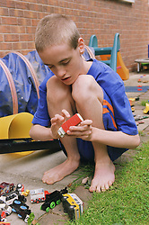 Teenage boy with autism crouching down outside in garden playing with toy truck,