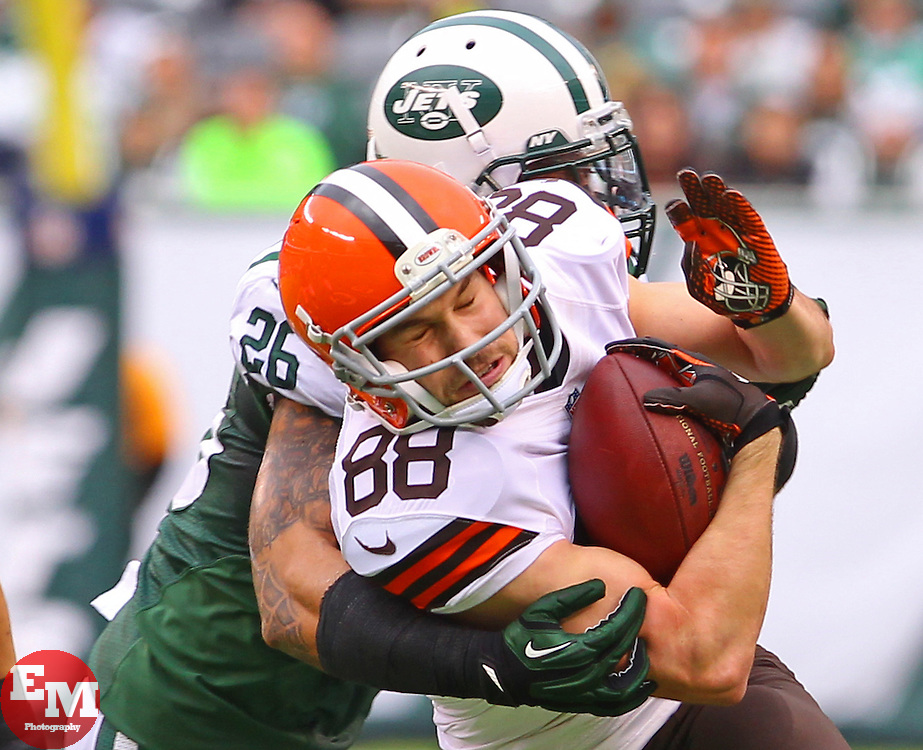 Dec 22, 2013; East Rutherford, NJ, USA; Cleveland Browns wide receiver Josh Cooper (88) breaks a tackle by New York Jets strong safety Dawan Landry (26) during the first half at MetLife Stadium.