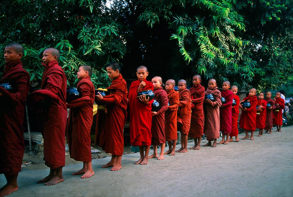 Monks receiving alms at Shwe Kyet Yet on Ayeyarwady River near Mandalay, Myanmar (Burma)
