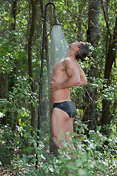 sexy man in an outdoor shower in the woods