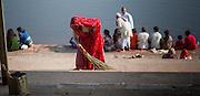 Indian woman in red sari sweeping Pushkar lake ghats (India)