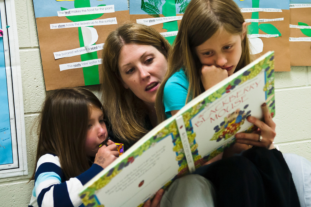 Lathan Goumas | MLive.com..Nicole Yambrick reads to her daughters Isabelle, 6, and EvelynYambrick, 8, during the seventh annual Author's Tea at Cool Elementary School in Grand Blanc Township, Mich. on Friday June 1, 2012. The event allows students to invite members of their family to the school and share with them a book of each student has written during the year.