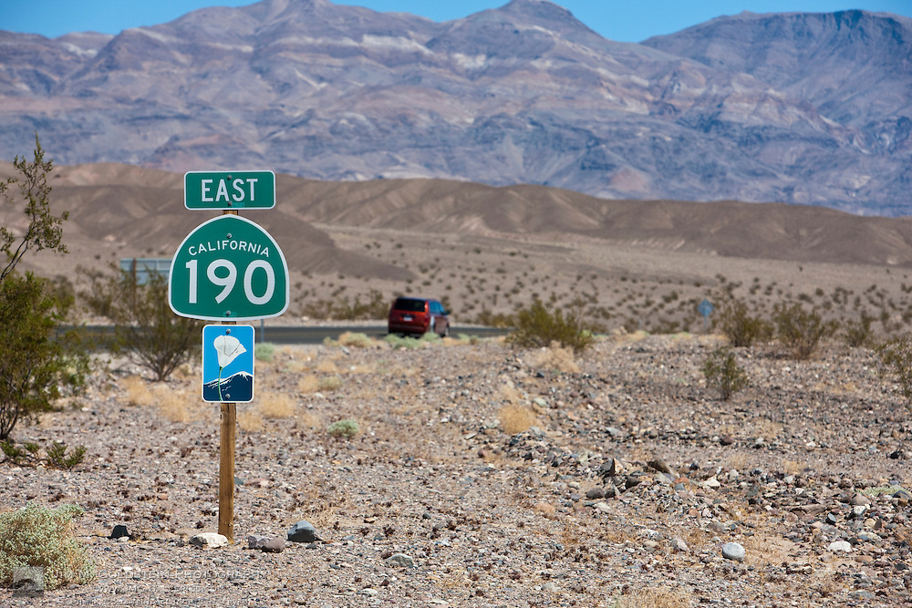 A minivan drives past a California state route 190 scenic byway sign- Death Valley National Park, California