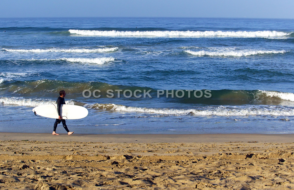 Man Walking Along the Beach With His Long Board Checking Out Waves