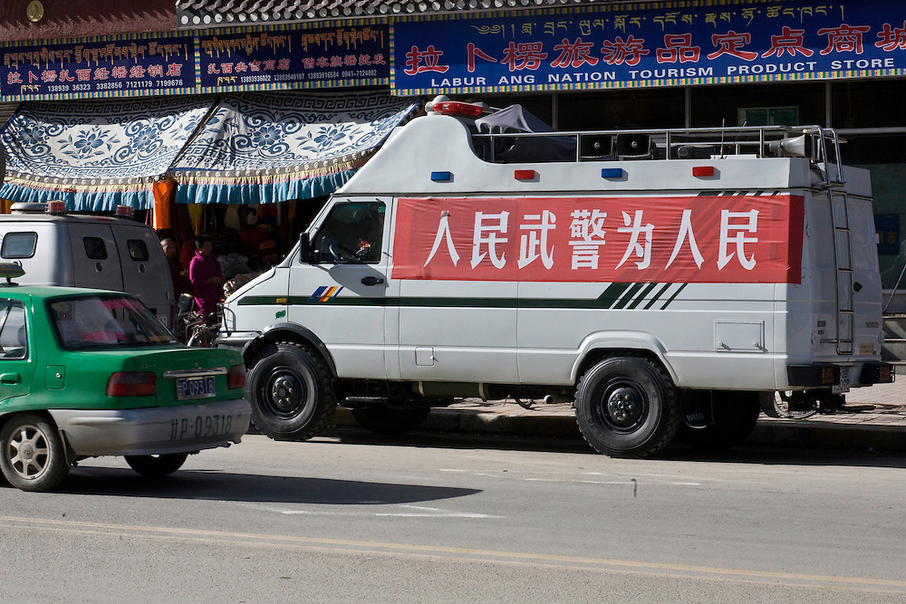 """Some vehicles of the People's Armed Police in the main street of Xiahe. the slogan says """"The People's army for the people !""""(Renmin wujing wei renmin !"""")."""
