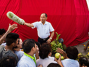 18 NOVEMBER 2015 - BANGKOK, THAILAND:  People grab food that was left as an offering at the chedi at Wat Saket at the start of the temple's annual fair. Wat Saket is on a man-made hill in the historic section of Bangkok. The temple has golden spire that is 260 feet high which was the highest point in Bangkok for more than 100 years. The temple construction began in the 1800s in the reign of King Rama III and was completed in the reign of King Rama IV. The annual temple fair is held on the 12th lunar month, for nine days around the November full moon. During the fair a red cloth (reminiscent of a monk's robe) is placed around the Golden Mount while the temple grounds hosts Thai traditional theatre, food stalls and traditional shows.     PHOTO BY JACK KURTZ