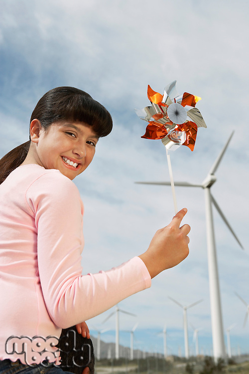 Girl (7-9) holding windmill, sitting on fathers shoulders at wind farm, portrait