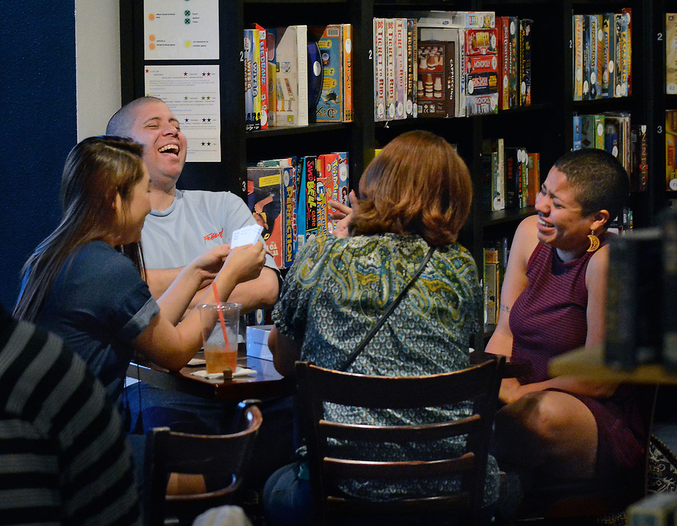 "jt050317m/spec sec/jim thompson/  left to right- Grallian Harbaugh and Myesha Dean crack up laughing as they play the game "" Cards Against Humanity""  with Gina Yi and Michaela Dean(center) at the Empire Board Game Library Wednesday night. Wednesday May. 03, 2017. (Jim Thompson/Albuquerque Journal)"
