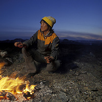 Russia, Koryuk Reindeer herder warms himself by campfire while guarding herd in Russian Far East's Taygonos Peninsula.