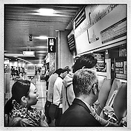 Train company security camera watches over customers as they purchase commuter train tickets.  Tokyo, Japan.