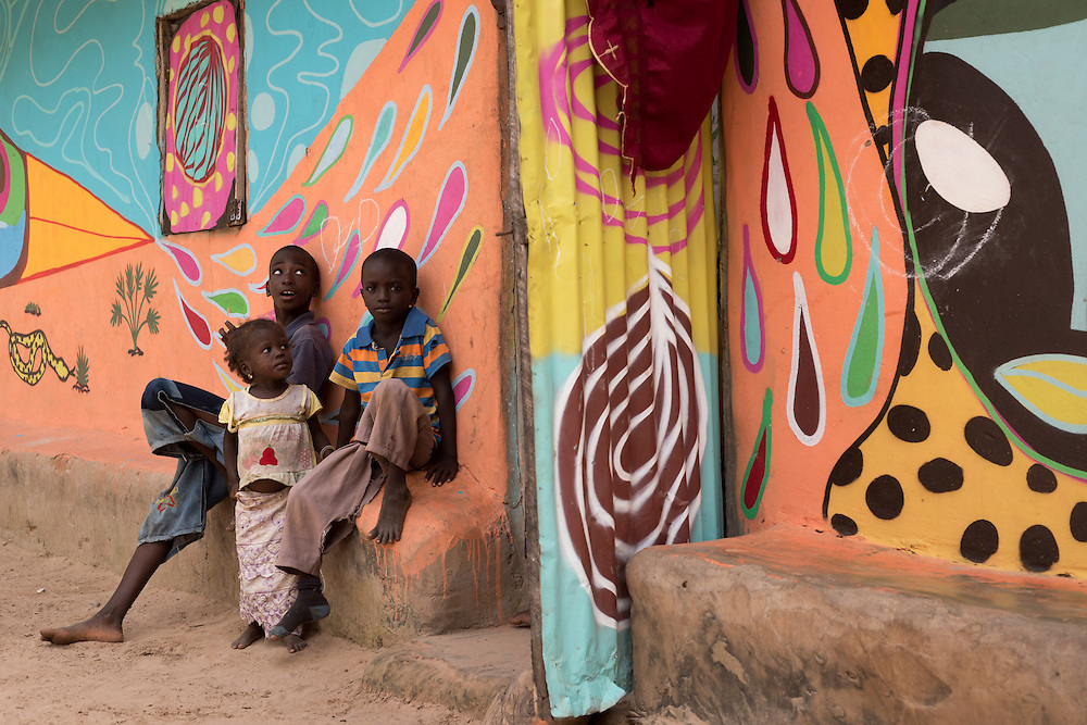 Children in front of their house, all painted with streetart, The Gambia.