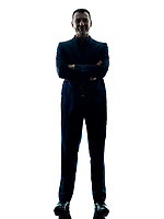 one caucasian business man standing arms crossed silhouette isolated on white background