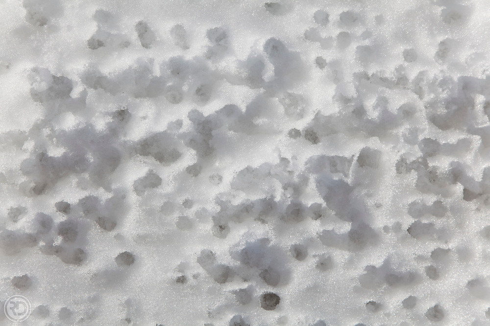 Snow mottled by dripping water
