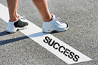 Man standing on stepping on white line with success sign