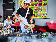 "18 MAY 2017 - BANGKOK, THAILAND: A chef at a street food stall on Yaowarat Road grills prawns. City officials in Bangkok have taken steps to rein in street food vendors. The steps were originally reported as a ""ban"" on street food, but after an uproar in local and international news outlets, city officials said street food vendors wouldn't be banned but would be regulated, undergo health inspections and be restricted to certain hours on major streets. On Yaowarat Road, in the heart of Bangkok's touristy Chinatown, the city has closed some traffic lanes to facilitate the vendors. But in other parts of the city, the vendors have been moved off of major streets and sidewalks.      PHOTO BY JACK KURTZ"
