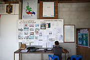 Supot Kalasong, 42, works in the communal meeting hall preparing documents to submit to Government agencies. Mr Supot was shot in April 2016 but survived.<br /> <br /> Since 2008, this community of around 70 families have been embroiled in a conflict with a palm oil company that locals allege has been trying to violently evict them. Since 2010, four members of the community have been shot dead and a fifth shot, but survived.<br /> <br /> For decades the palm oil company Jiew Kang Jue Pattana Co., Ltd has illegally occupied and cultivated palm oil trees on a 535-acre plot of land in the Chai Buri District of Surat Thani Province. <br /> <br /> The company operated with no official legal documentation or land concession, until the Southern Peasant's Federation of Thailand (SPFT), who supports the community, began investigating them and collecting evidence.<br /> <br /> This evidence ultimately lead to a Supreme Court ruling against the company for illegal trespassing and land encroachment. But the community still struggles to remain on the land to this day with the last shooting happening in April 2016, years after the court case was won.