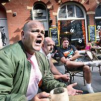 Nederland, Nederland , 1 juli 2010..Verontwaardigde en boze marktlieden bij cafe Marktzicht vanmorgen op de ten KateMarkt..De Ten Katemarkt was vandaag een treurige aangelegenheid. Minstens de helft van de kramen was onbezet. De kooplieden protesteerden tegen het feit dat er vandaag maar een kramenverhuurder is. Hun eigen Vereniging van Kooplieden is door stadsdeelbestuurder Bouwe Olij op een van zijn laatste werkdagen buitenspel gezet. Olij meende dat de vereniging  te machtig werd op de markt, die niet goed loopt en een eenzijdig aanbod van groente en fruit heeft..Indignant and angry market traders in the cafe this morning at terrace Marktzicht at theTen Kate Market. A town manager has put their union out of play.