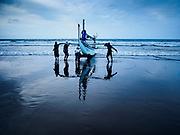 29 JULY 2017 - AIRKUNING, BALI, INDONESIA: Villagers land an outrigger fishing canoe after it returned from a night's fishing in the Indian Ocean in Airkuning, a Muslim fishing village on the southwest corner of Bali. Villagers said their regular catch of fish has been diminishing for several years, and that are some mornings that they come back to shore with having caught any fish.    PHOTO BY JACK KURTZ