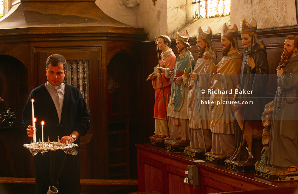 Watched by statues of saints, a priest lights candles before Sunday Mass in a local Catholic church in rural Normandy.
