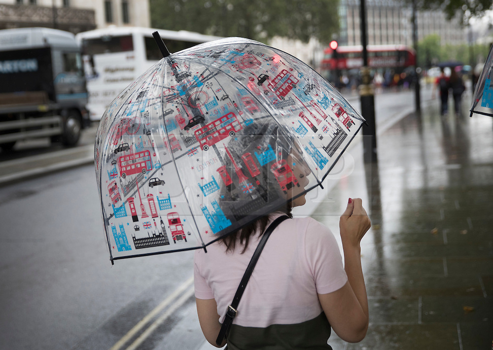 © Licensed to London News Pictures. 02/08/2016. London, UK. A visitor with a London themed umbrella walks near Parliament as intermittent rain showers hit the capital. Photo credit: Peter Macdiarmid/LNP