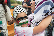 During a vigil held in Montreal in solidarity with the people of Gaza, a woman carries her child in her arms whose face is painted with a Palestinian flag.