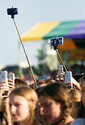 02 May 2015. New Orleans, Louisiana.<br /> The New Orleans Jazz and Heritage Festival. <br /> Selfie sticks with phones upload Ed Sheeran live as he wows fans at the Gentilly stage.<br /> Photo; Charlie Varley/varleypix.com