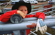 05 AUGUST 2000 - WILLIAMS, AZ: A young cowboy watches the livestock chutes and wait for the action to begin at the 22nd Annual Cowpunchers' Reunion Rodeo in Williams, Arizona, Aug 5.  The Cowpunchers' Reunion Rodeo is held for working cowboys from the ranches in Arizona and the region. PHOTO BY JACK KURTZ