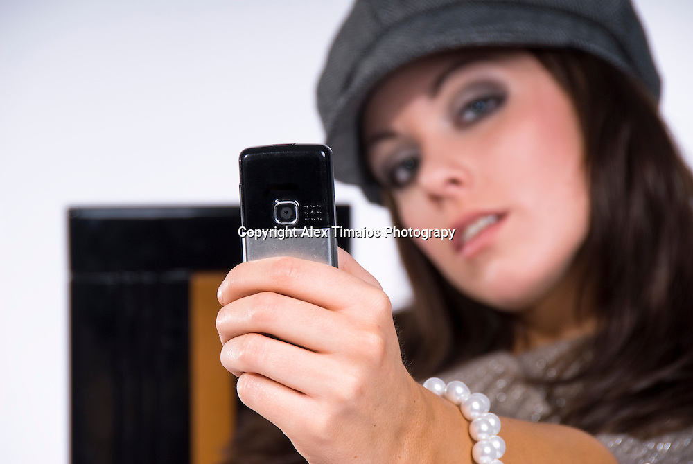 Young lady taking a photo with her mobile phone
