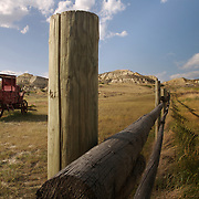 "An old abandoned stagecoach shares the landscape with a wooden fence that stretches towards North Dakota's Badlands near Medora.  ..The stark prairie landscape, with it's towering buttes, jaw-dropping chasms and surreal spires, is the gateway to the ""Old West""...Nearby Theodore Roosevelt National Park draws thousands of visitors each year to North Dakota's western border.  photo by David Peterson.."