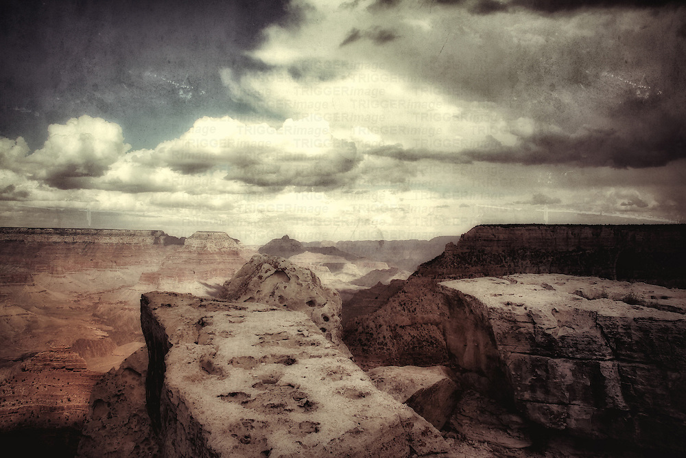 Large rocks in the foreground looking across the Grand Canyon in USA with clouds in a blue summer sky with texture layer