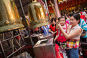 31 JANUARY 2014 - BANGKOK, THAILAND:   A woman and her baby ring prayer bells at the Poh Teck Tung Shrine during Lunar New Year festivities, also know as Tet and Chinese New Year, in Bangkok. This year is the Year of the Horse. Ethnic Chinese make up about 14% of Thailand and Chinese holidays are widely celebrated in Thailand.     PHOTO BY JACK KURTZ